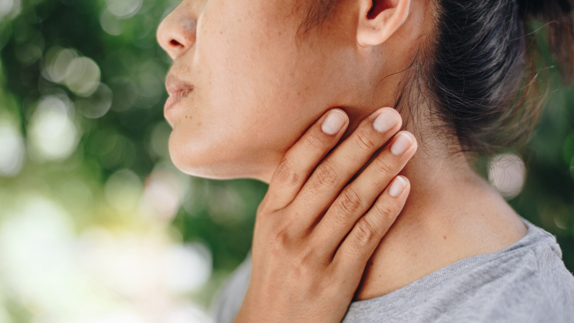 Woman with sore throat touches neck wonder if it is head and neck cancer | cCARE | San Diego & Fresno, CA