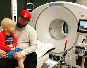 Jaxson with his dad by a large imaging machine while treating against Rhabdomyosarcoma | cCARE | Fresno & San Diego, CA
